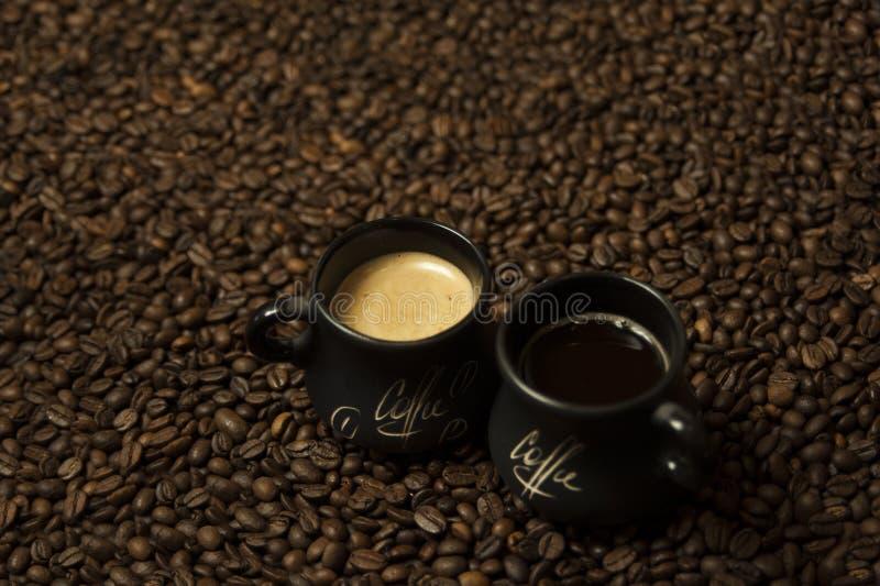 Une tasse de café noir avec du lait se tenant sur des grains de café Un concept sain de déjeuner photo stock
