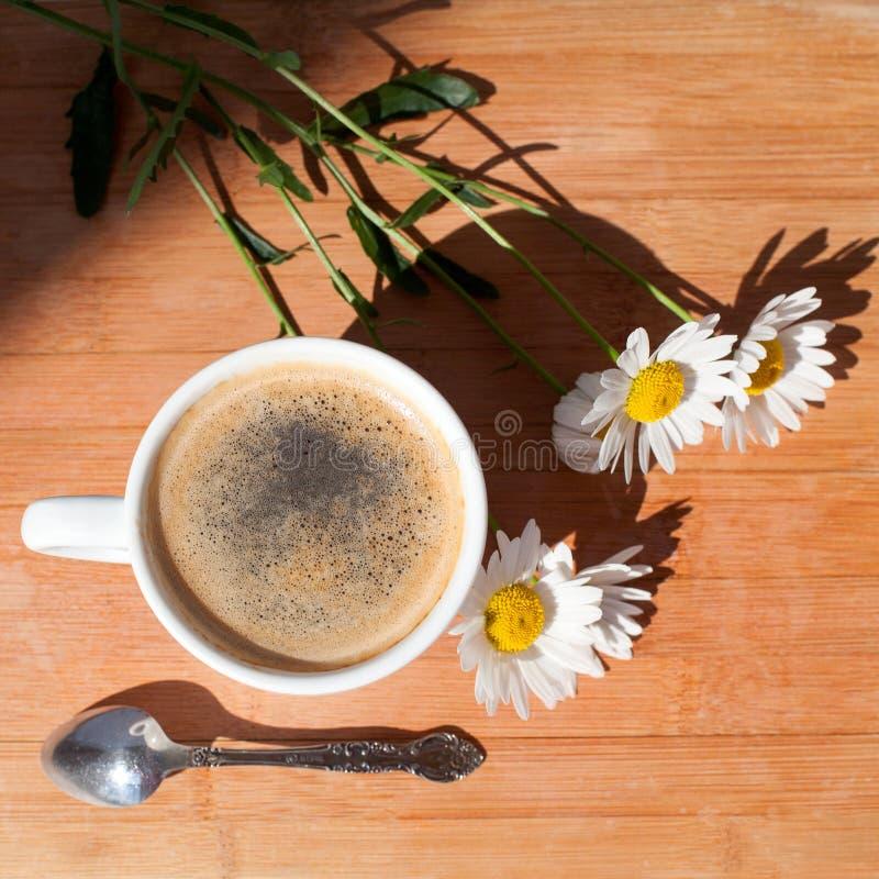 Une tasse de café noir, cuillère d'argent, branche des fleurs de marguerite blanche sur la vue supérieure de fond en bois photo libre de droits