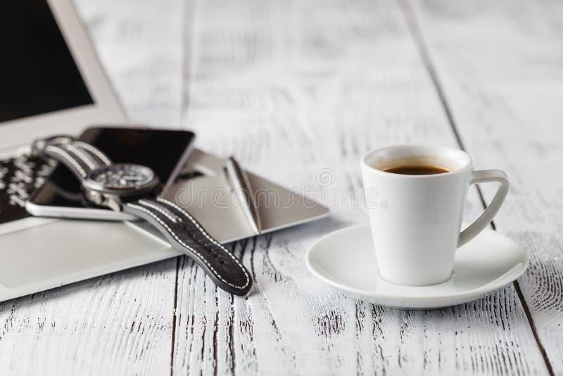 Une tasse de café noir et d'équipements occasionnels d'affaires sur le conseil en bois photos stock