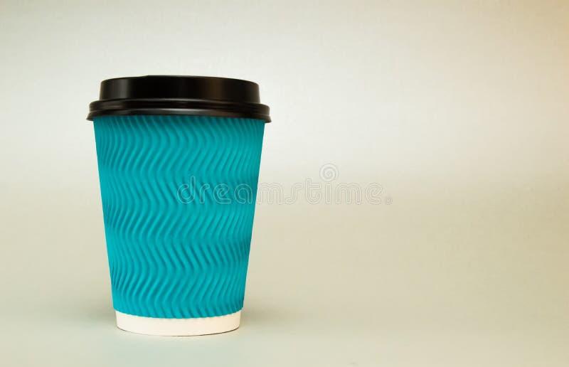Une tasse de café de papier bleue avec un couvercle noir sur un fond clair image stock