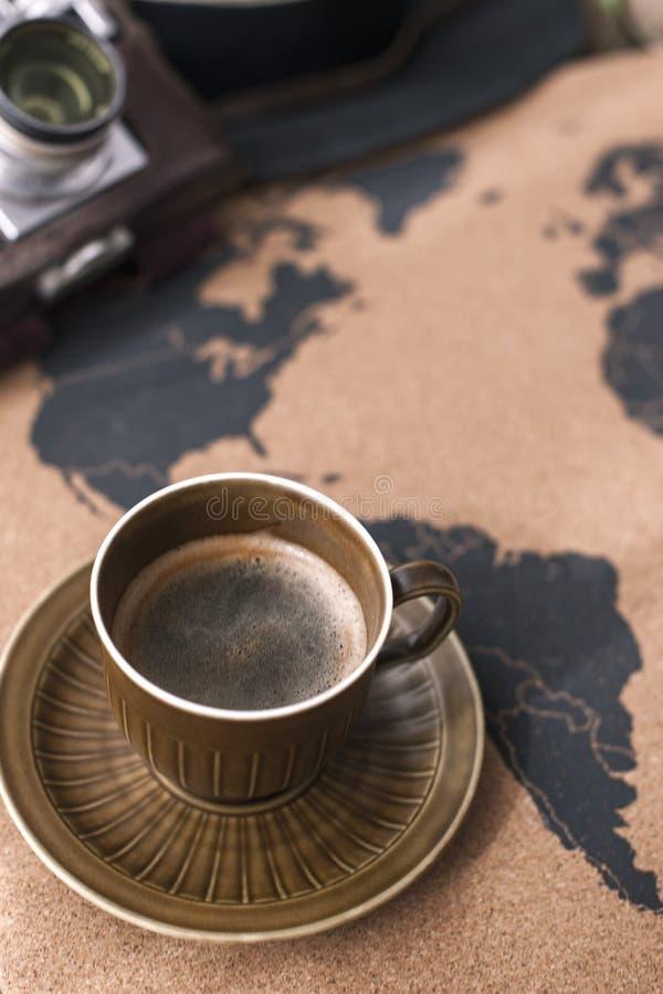 Une tasse de café parfumé sur la carte, une vieille caméra et un itinéraire p photo libre de droits