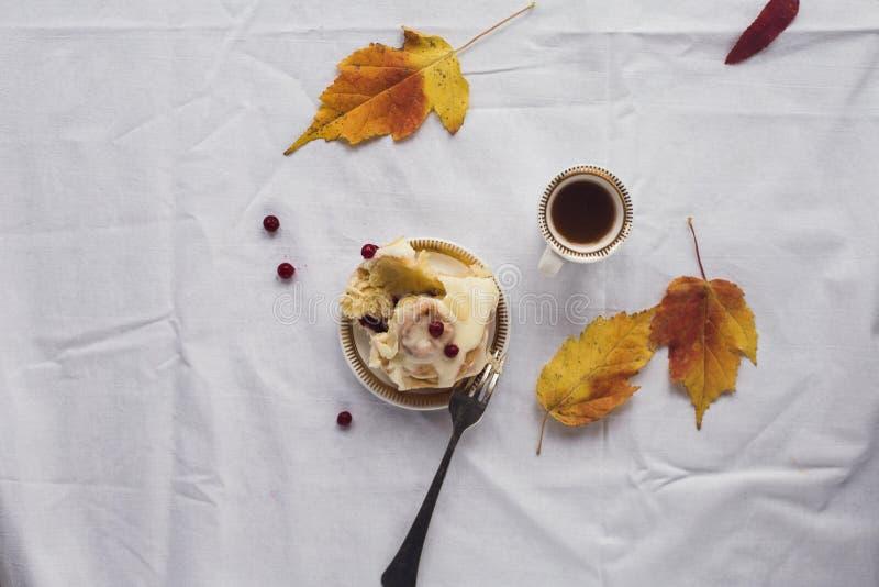 Une tasse de café, de petit pain de cannelle et de feuilles jaunes photo stock