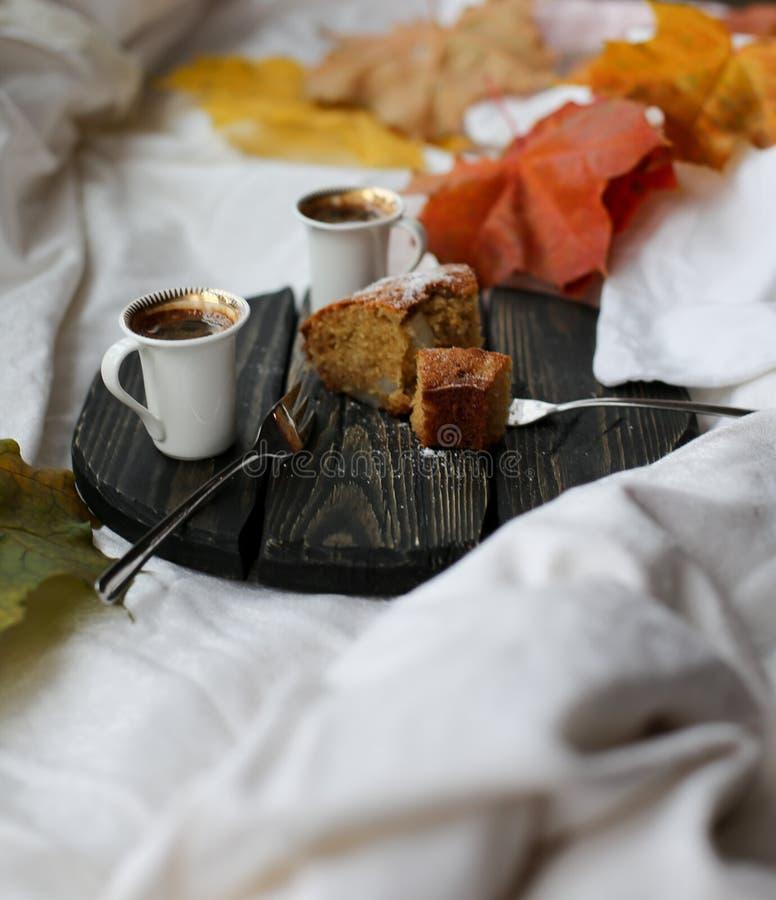 Une tasse de café, de petit pain de cannelle et de feuilles jaunes image stock