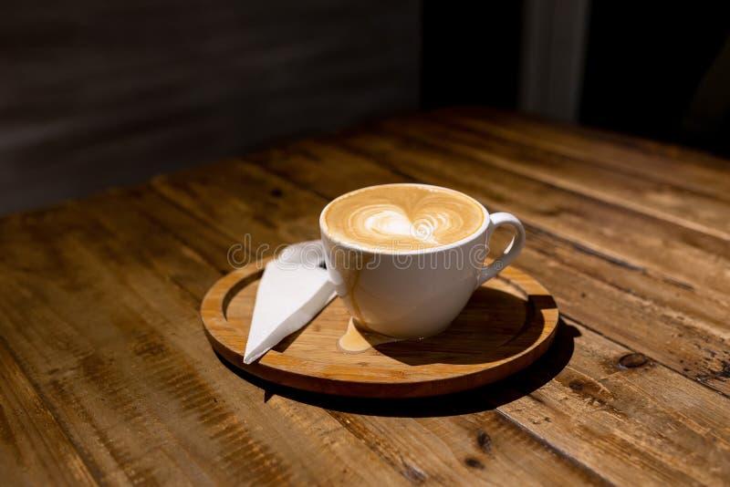 Une tasse de café renversé d'un plat en bois image stock