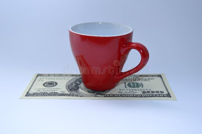 Une tasse de café rouge est sur un billet d'un dollar 100 photos libres de droits