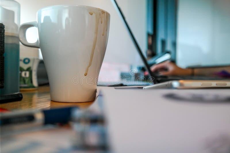 Une tasse de café sur le bureau de travail avec le travail stationnaire et l'ordinateur portable à l'arrière-plan photographie stock libre de droits