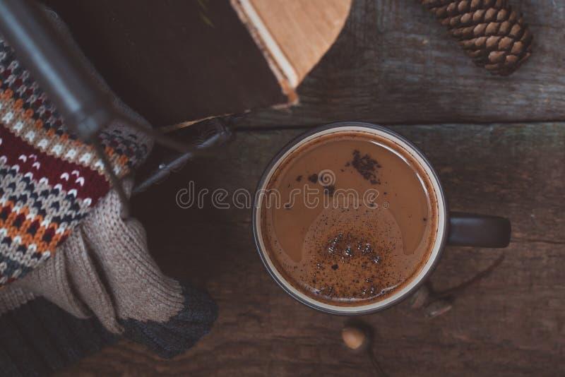 Une tasse de café sur le fond en bois Repassez le panier avec un chandail et un vieux livre toned photographie stock libre de droits