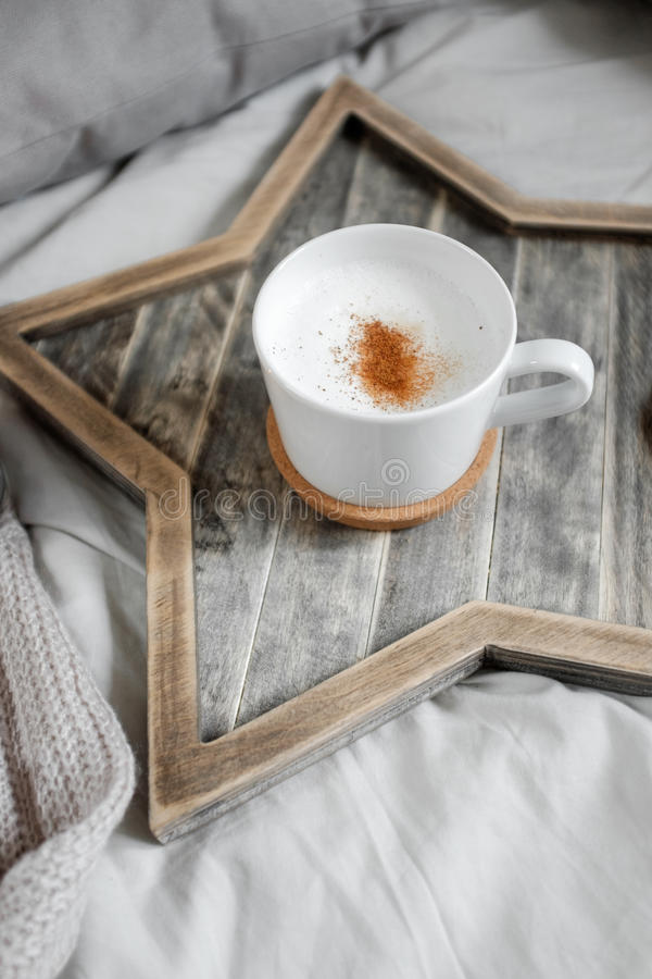 Une tasse de café sur un plateau en forme d'étoile en bois scandinave photos stock