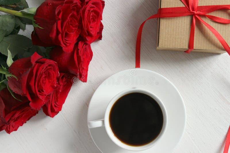 Une tasse de café, un bouquet des roses rouges et un cadeau avec un ruban rouge sur le plan rapproché de table photographie stock libre de droits