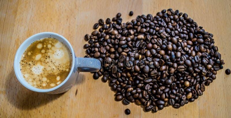 Une tasse de caf? et une pile des grains de caf? images libres de droits