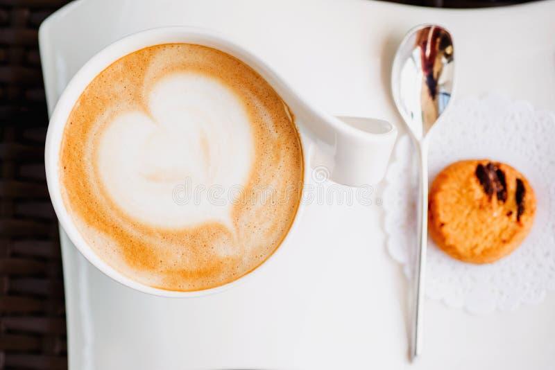 Une tasse de cappuccino avec un modèle sur la mousse Boisson de matin dans une belle tasse sur un fond clair image stock