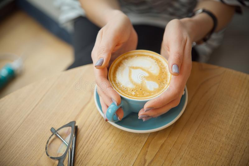 Une tasse de cappuccino dans les mains d'une fille Matin avec du café Le barman se prépare au cappuccino photos libres de droits