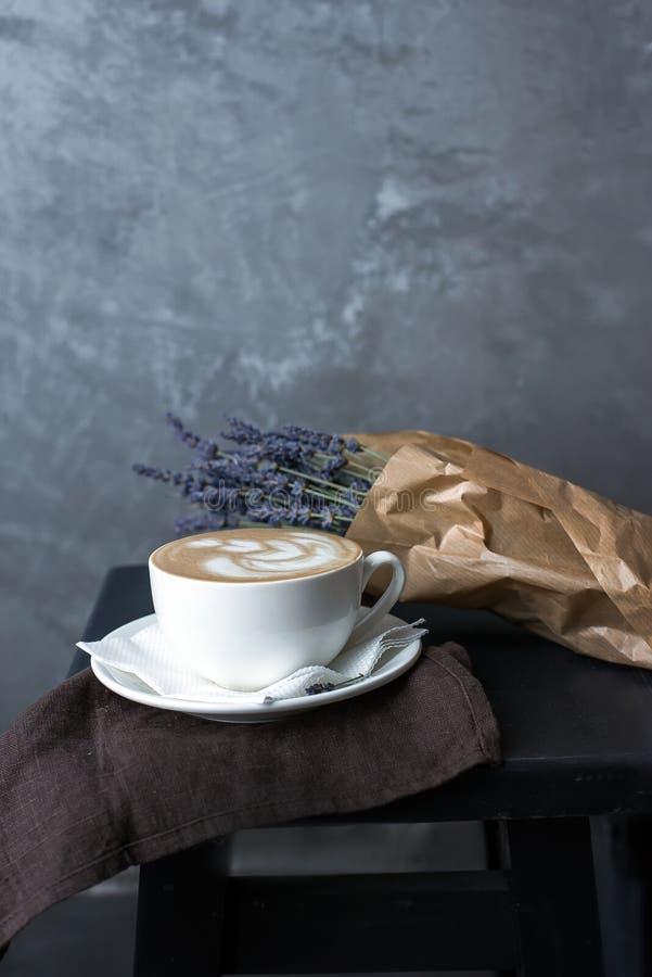Une tasse de cappuccino sur une serviette brune avec la lavande image libre de droits