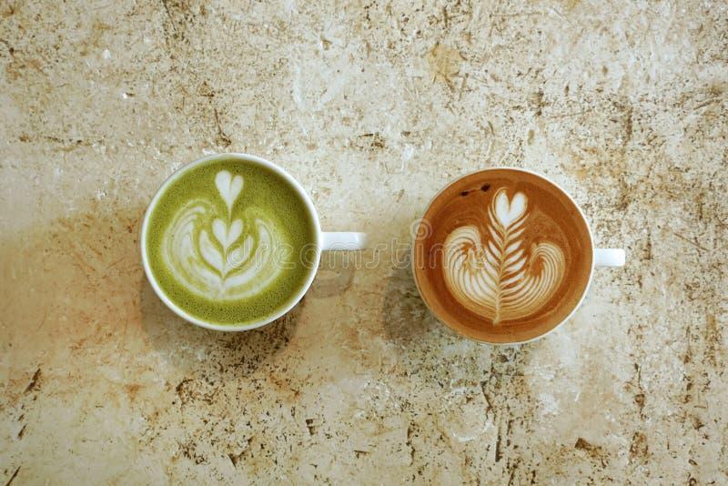 Une tasse de latte de matcha de thé vert et tasse de café d'art de latte photographie stock libre de droits