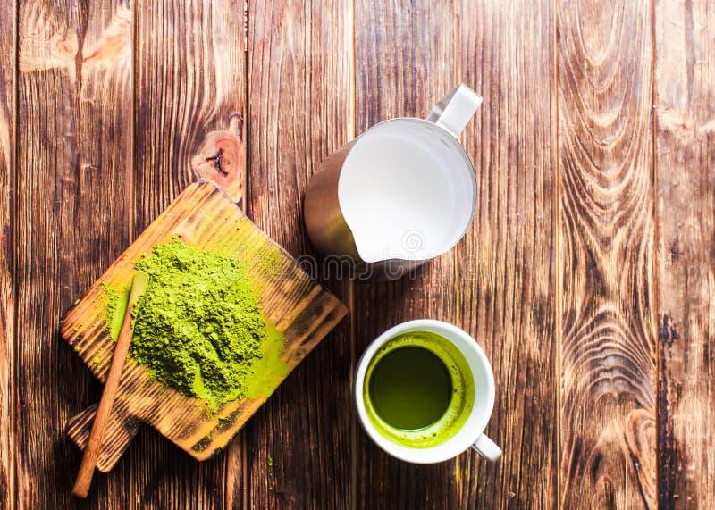 Une tasse de thé au lait de Matcha la cruche et de thé vert en poudre sur la table en bois photos libres de droits