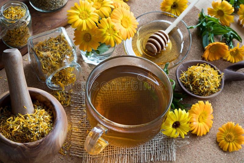 Une tasse de thé de calendula avec le calendula à l'arrière-plan images stock