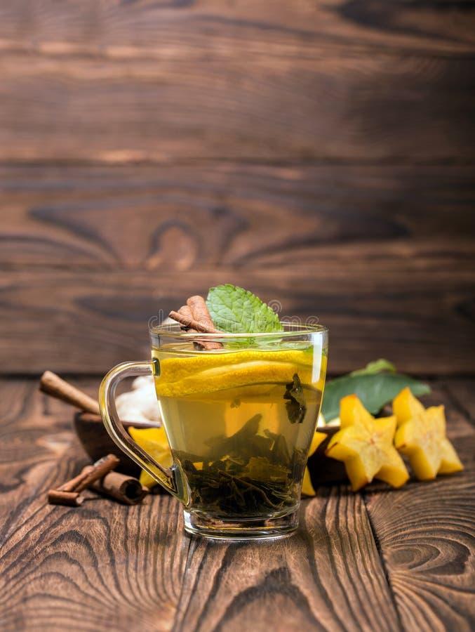 Une tasse de thé de citron avec la menthe sur un fond brouillé en bois Thé chaud avec des bâtons de carambolier et de cannelle Co photos libres de droits