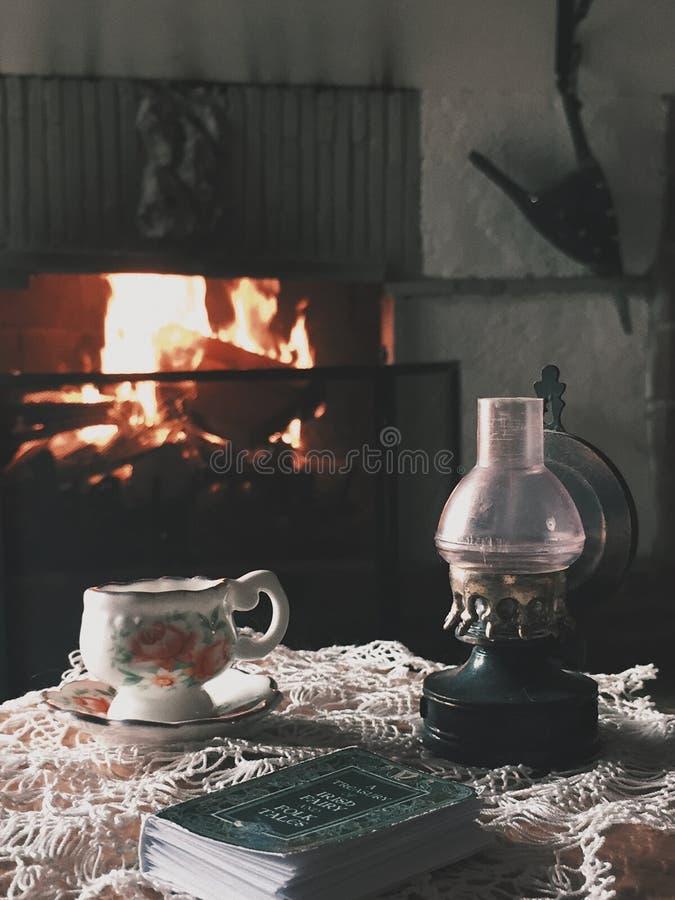 une tasse de thé et un livre par la cheminée images libres de droits