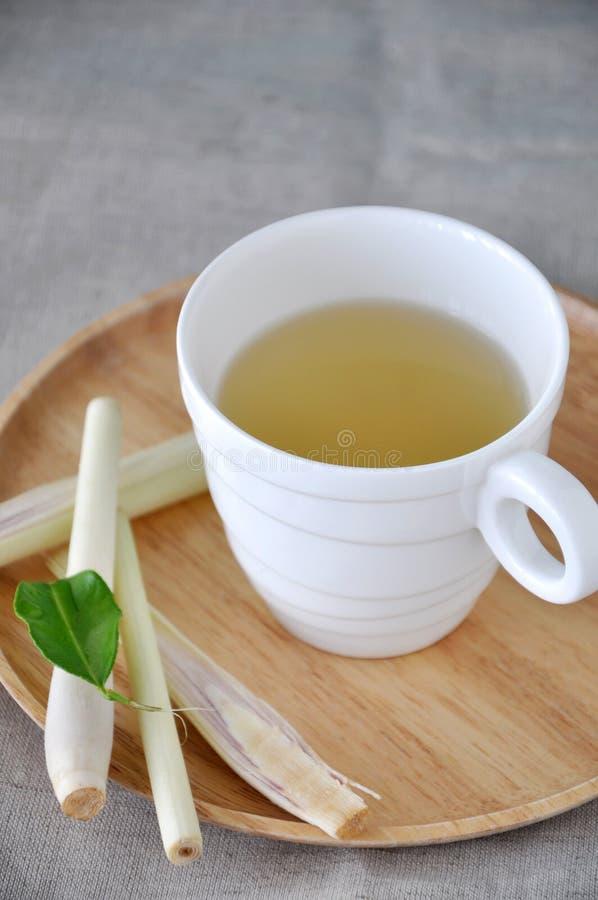 Une tasse de thé frais de schénanthe de plat en bois images stock
