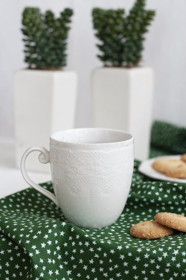 Une tasse de th? noir sur une serviette, biscuits faits maison, une paire d'usines d?coratives dans un pot sur le fond blanc images stock