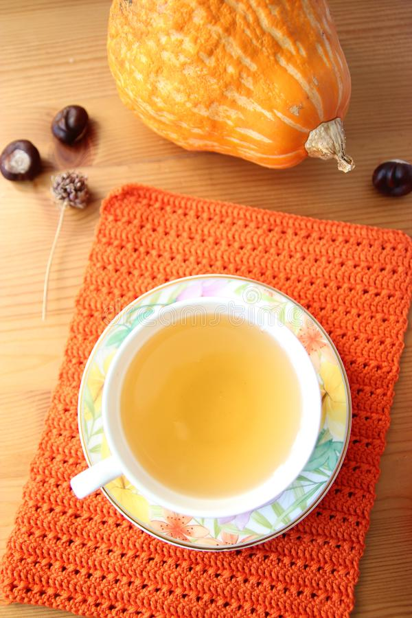 Une tasse de thé sur l'orange a tricoté le tapis et le potiron sur la table en bois photo stock