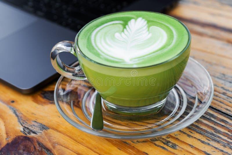Une tasse de thé vert de lait chaud sur la table images libres de droits