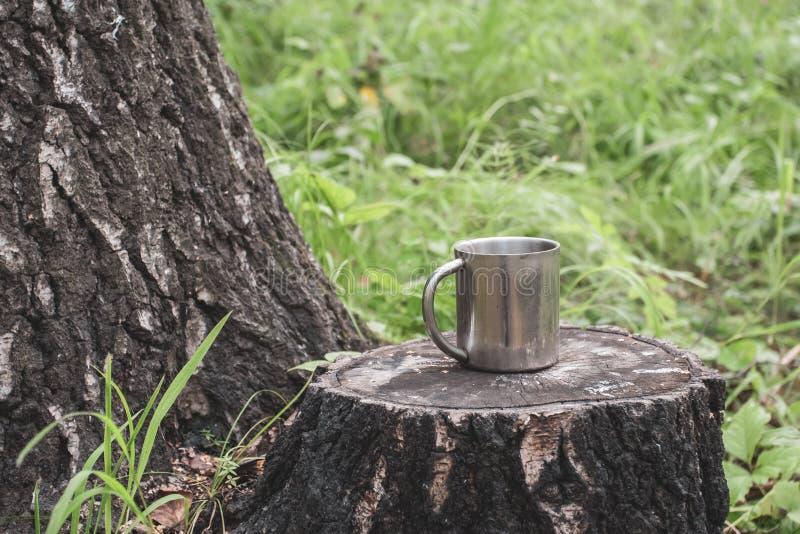 Une tasse de touristes de fer se tient sur un tronçon dans une forêt à côté d'un arbre épais sur un fond d'herbe brouillée photos libres de droits
