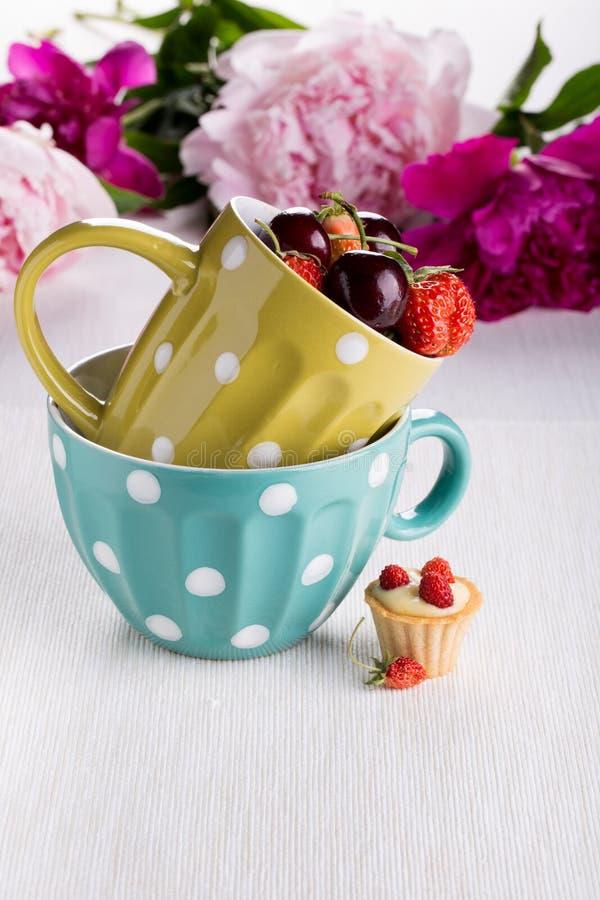Une tasse des baies fraîches et de la mini tartelette image stock