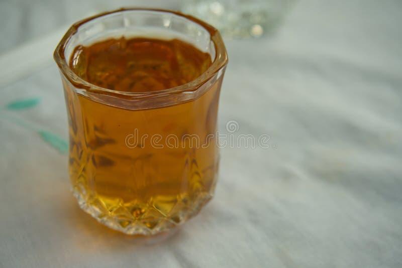 Une tasse en verre de sirop d'?rable mise sur la table photos libres de droits
