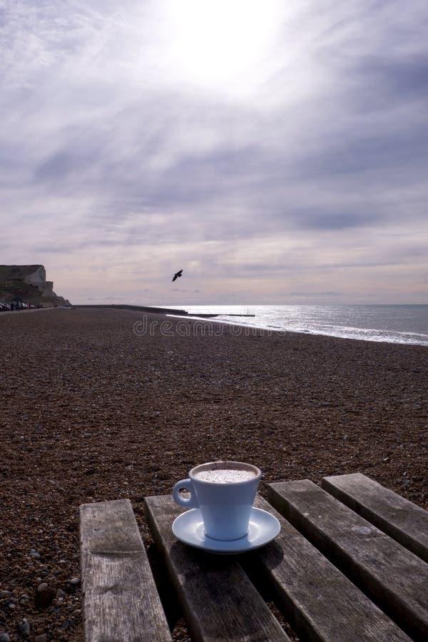 Une tasse et soucoupe de café blanc sur une table avec un Pebble Beach, une mer et un ciel dans le backgroundcino sur la plage photos stock