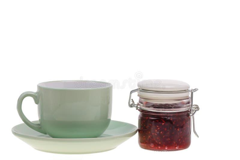 Une tasse et un pot de confiture sur le blanc photo stock