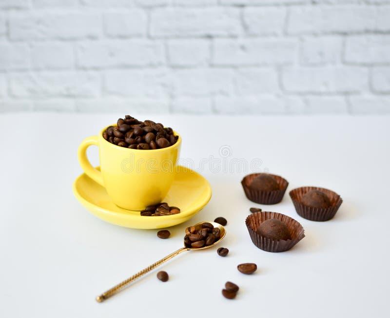 Une tasse jaune avec les grains de café naturels, sur un fond blanc, et des chocolats Cuillère de vinyle Le concept du matin photo stock