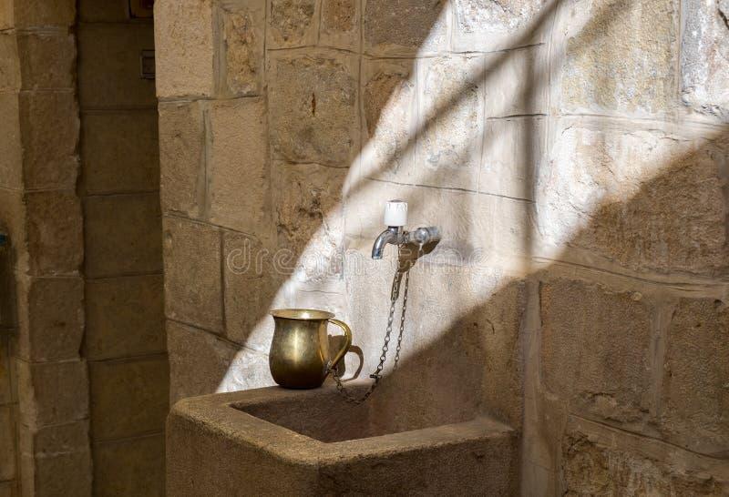 Une tasse pour le rituel lavant à la main juif à côté de l'entrée de sinagogue images libres de droits