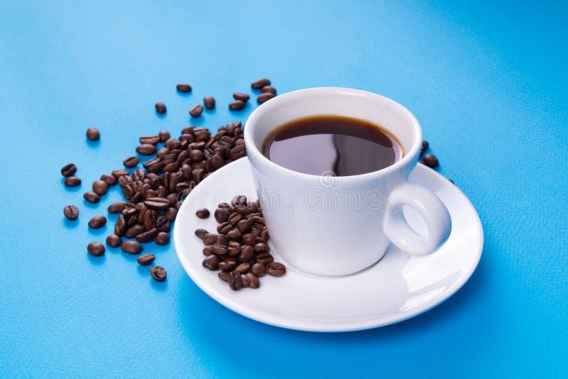 Une tasse se tient sur une soucoupe à côté d'une pile des grains de café réglés tous sur un fond bleu avec un beau point culminan images libres de droits
