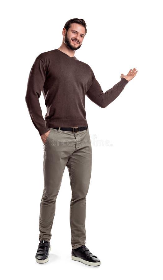 Une tenue de détente d'homme fait une étape courte, sourit et montre quelque chose avec un de ses bras sur un fond blanc photos libres de droits