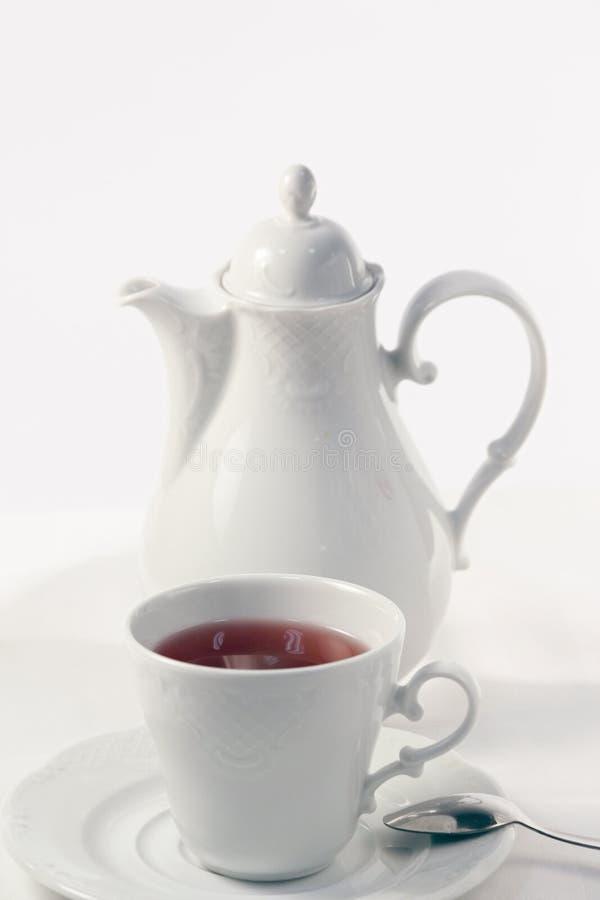 Une théière blanche, une tasse blanche de thé de fruit et une cuillère à café du plat blanc photographie stock