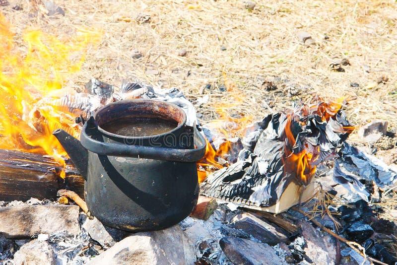 Une théière fumée noire se tient sur le feu entouré par les langues jaunes de flamme dans la perspective de l'herbe sèche - inven photos libres de droits