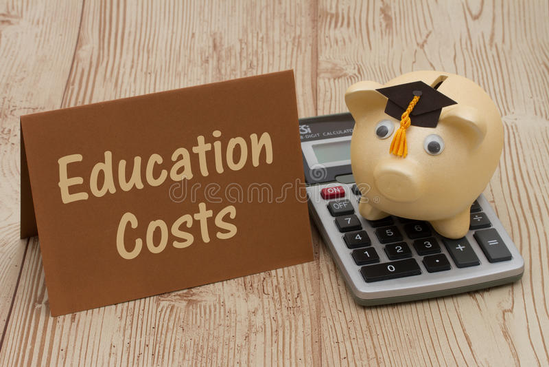 Une tirelire d'or avec le chapeau, la carte et la calculatrice de diplômé sur le bois b image libre de droits