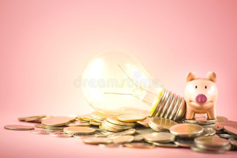 Une tirelire ou une ampoule sont pile sur la pile de pièces de monnaie pour le concept économisant d'argent Idée créative de fina image stock