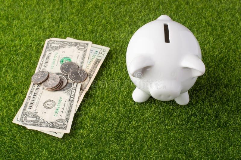 Une tirelire sur un fond d'herbe avec des dollars et des pièces de monnaie quartes Un concept d'argent économisant ?conomie Vue d photos libres de droits