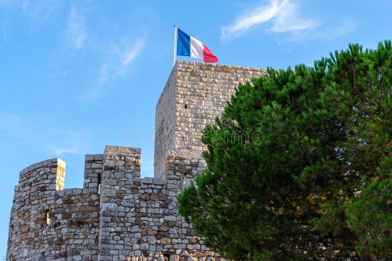 Une tour antique de Cannes avec le drapeau français photos libres de droits