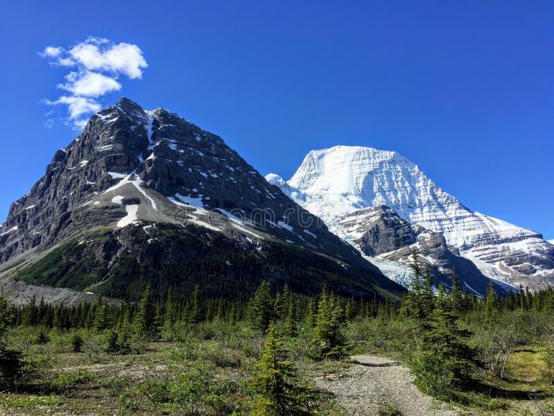 Une traînée à distance menant vers deux montagnes énormes, une couverte dans la neige et une pas Il y a un glacier entre les mont photo stock