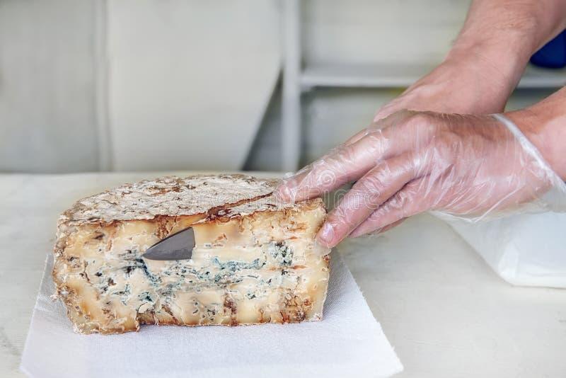 Une tranche de fromage âgé bleu de stilton d'épicerie fine sur une table blanche Le vendeur coupe un morceau de la tête de fromag photographie stock libre de droits