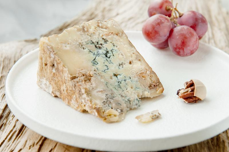 Une tranche de fromage âgé bleu de stilton sur une table en bois Du fromage est servi avec des grands raisins Qualité des produit images stock