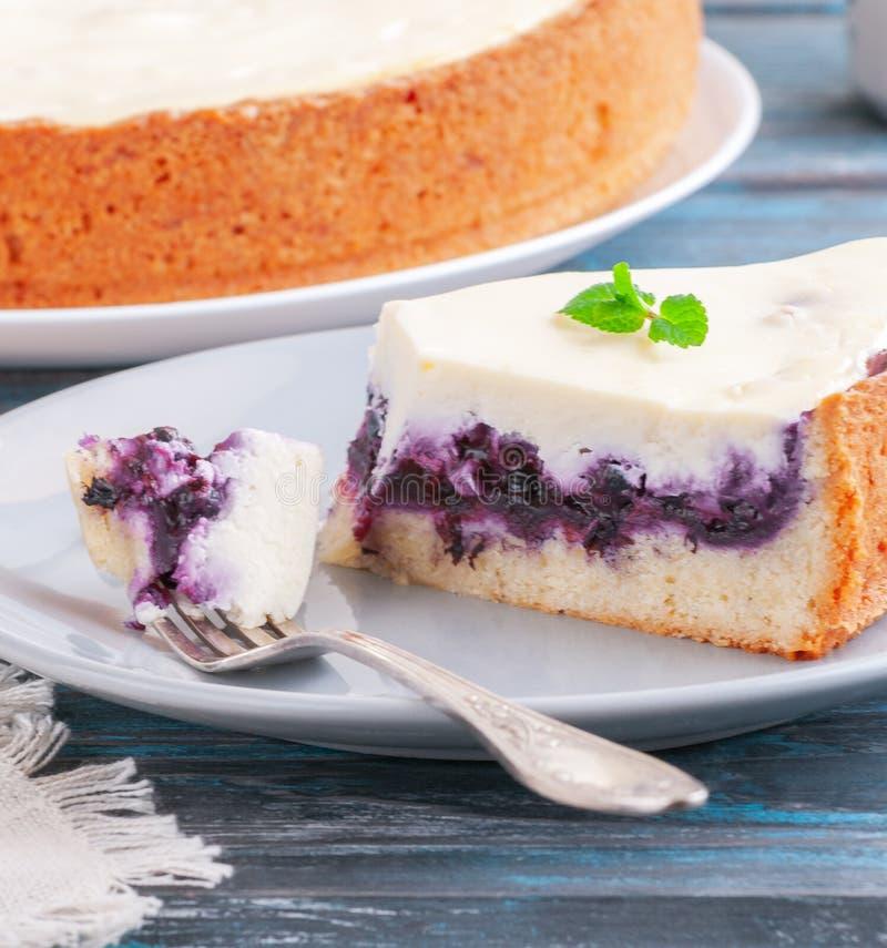 Une tranche de gâteau au fromage de myrtille avec la menthe sur une fourchette De la plaque Fond en bois bleu-foncé Plan rapproch photo stock
