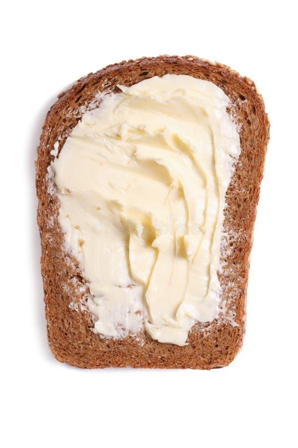 Une tranche de pain de seigle avec la fin de beurre sur le blanc photo libre de droits