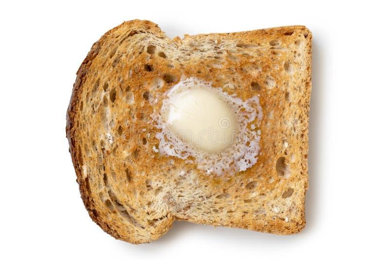 Une tranche simple de pain grillé de blé entier avec un bouton de butte de fonte image stock