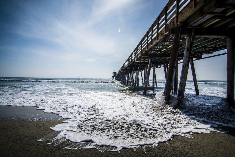 Une vague se précipite sur le sable sous le pilier impérial de plage à San Diego, la Californie photographie stock