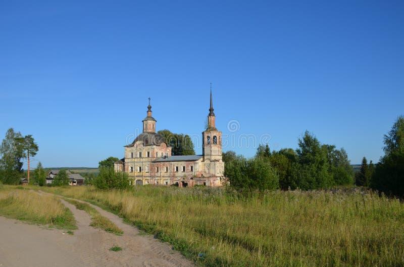 Une vieille église délabrée envahie avec des arbres dans la campagne contre un ciel bleu avec des nuages entourés par la verdure photo libre de droits