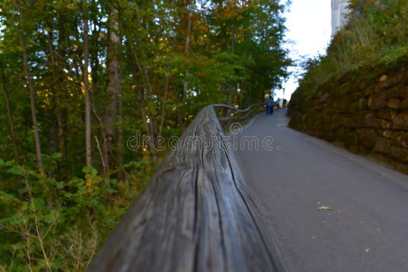 Une vieille barrière en bois le long de la route passe à l'infini par la nature images libres de droits